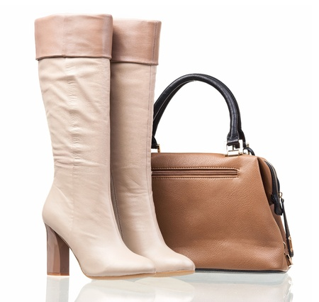 Women high-heeled boots and leather bag over white