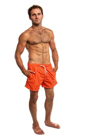 hombre sin camisa: Muscular hombre joven en traje de baño de pie sobre fondo blanco Foto de archivo