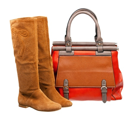 Pair of knee-high female boots and handbag over white  photo