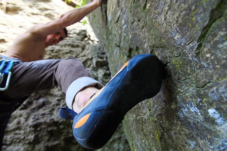 rock bottom: Rock climber about to start climbing his route, bottom view with his foot on the foreground  Stock Photo