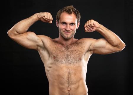 waistup: Waist-up portrait of muscular man flexing his biceps against black background