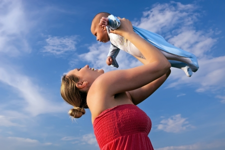 blond boy: Happy young mother lifting her baby boy high up against blue sky background
