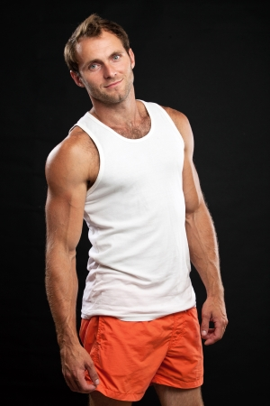 undershirt: Muscular young man standing on black background and smiling