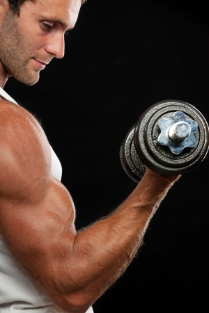Muscular man lifting dumbbell on black background Stock Photo - 17729464