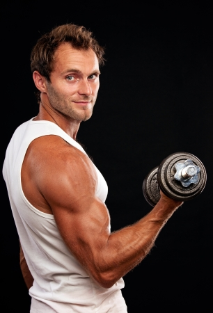 strong arm: Muscular man lifting dumbbell on black background