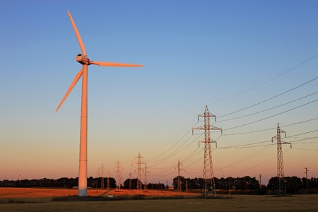 Electricity pylons and wind turbines against sky at sunset Stock Photo - 17755828