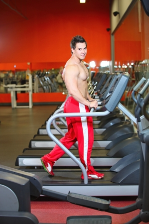 Young muscular guy working out on a treadmill  photo