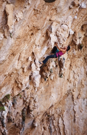 rock climb: Female rock climber on a cliff face