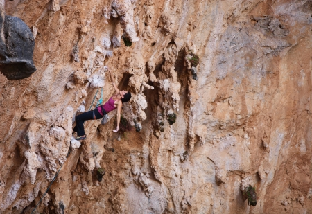 cliff face: Female rock climber on a cliff face