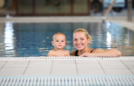 Young cheerful mother and little son in a swimming pool  photo