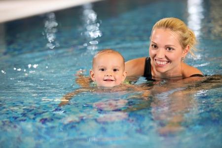 Jonge vrolijke moeder en zoontje genieten van zwemmen in een zwembad Stockfoto
