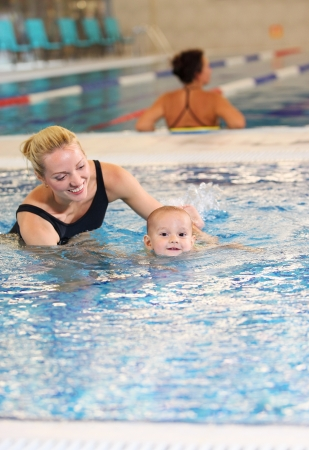 baby swimming: Young mother and little son in a swimming pool