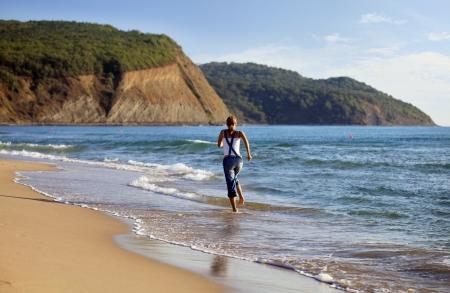 bulgaria girl: Young Caucasian woman jogging on the beach