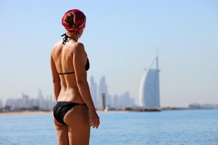 united arab emirates: Rear view of young woman on Jumeira beach, with famous luxurious Burj Al Arab Hotel in distance, Dubai, UAE