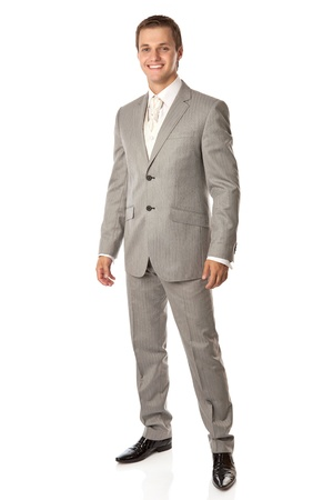 Full length of a young man in a suit smiling brightly, over white background photo