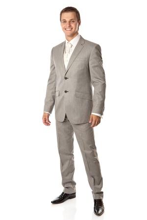 lazo negro: Longitud total de un hombre joven en un traje sonriendo alegremente, sobre fondo blanco