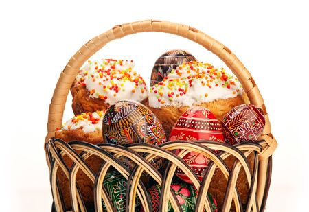 Basket with Easter cakes and painted eggs over white background  photo