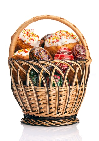 paskha: Basket with Easter cakes and painted eggs over white background  Stock Photo