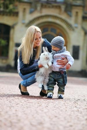 mamma e figlio: Giovane donna che mostra un coniglio fantasia al figlio