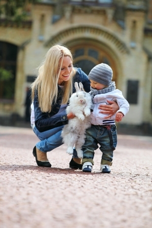blonde mom: Young woman showing a fancy rabbit to her son  Stock Photo