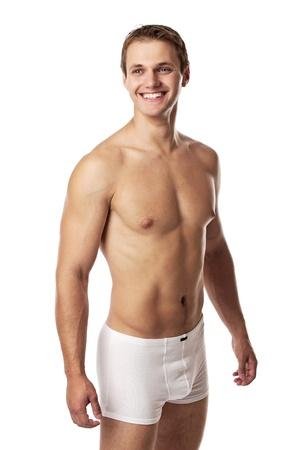 Knappe jonge man in ondergoed tegen een witte achtergrond Stockfoto