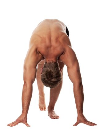 Muscular young guy getting ready for race over white background  photo