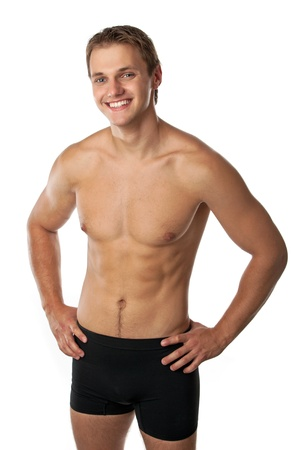 male torso: Cheerful young man in trunks over white