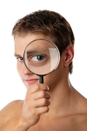 Cute young man without a shirt looking through a magnifying glass photo