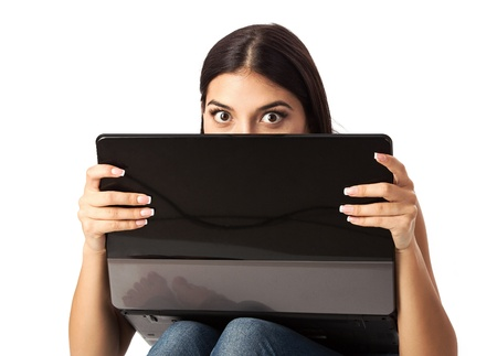 Young beautiful woman looking over a laptop against white background  photo
