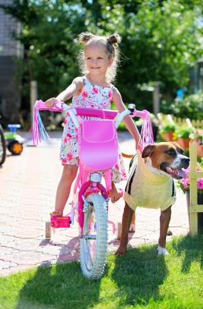american staffordshire terrier: Cute four-year old girl on a bicycle with her staffordshire terrier dog