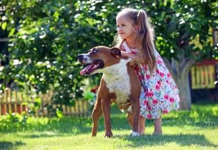 Cute vier jaar oud meisje speelt met haar Staffordshire terrier hond in voortuin