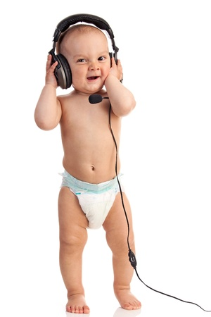 Portrait of a cute one-year old boy wearing a headset against white background