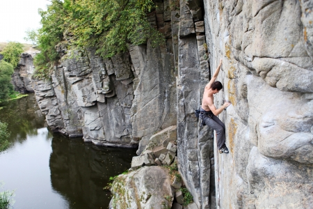 Rock climber on a cliff over a canyon river  photo