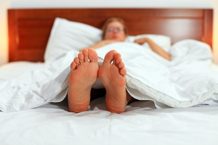 bare body women: Young caucasian woman lying down in bed, feet in focus  Stock Photo