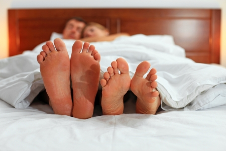 girl soles: Two pairs of male and female feet seen from under the blanket Stock Photo
