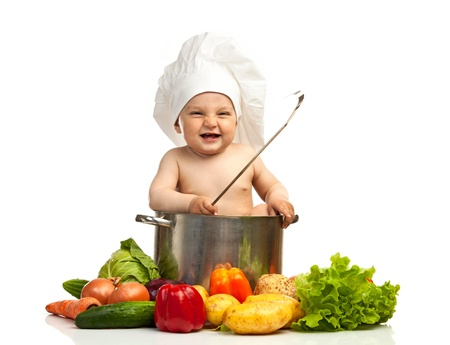 Little boy in chef s hat with ladle, casserole, and vegetables  photo