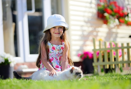Cute four-year girl smiling brightly and stroking her cat, looking at camera, outdoors  photo