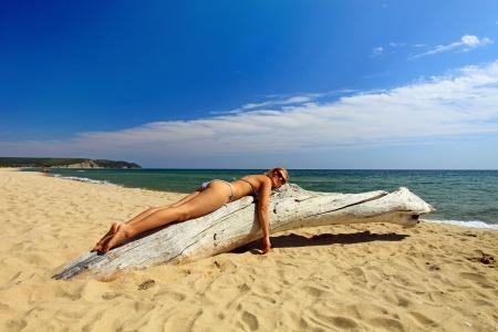 Beautiful young woman sunbathing on dry tree at wild beach photo