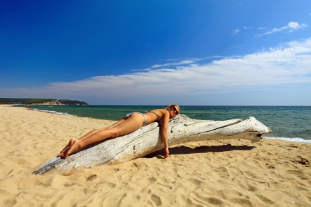 bulgaria: Beautiful young woman sunbathing on dry tree at wild beach Stock Photo