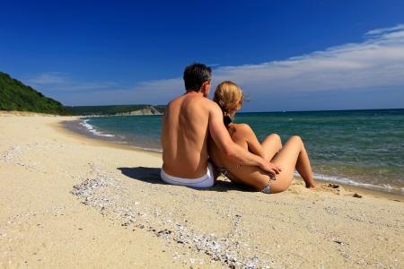 Achteraanzicht van de jonge Kaukasische paar op het strand Stockfoto