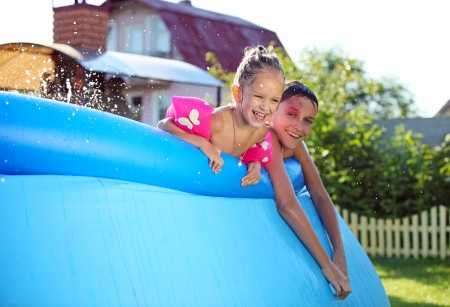 Joyful Caucasian siblings swimming in a inflatable swimming pool and looking at the camera