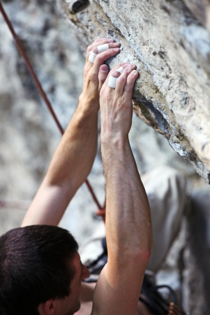 handhold: Closeup view of a rock climber s hands on a cliff  Stock Photo