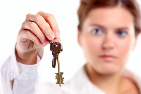 Extend: Young caucasian woman holding keys  Image with shallow depth of field, the keys in focus