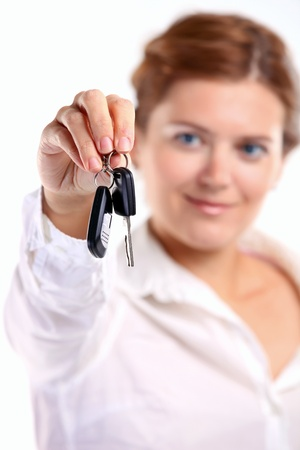 Friendly young woman holding car key  Image with shallow depth of field  The key is in focus   photo