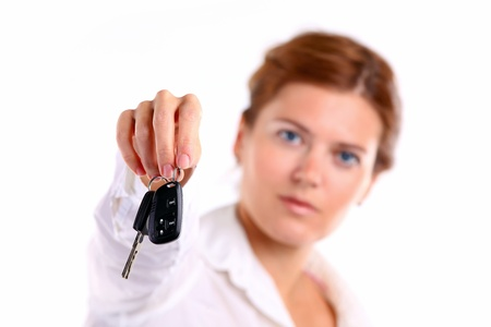 Young caucasian woman holding car key  Image with shallow depth of field  The key is in focus   photo