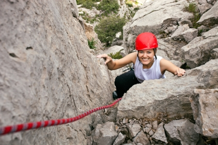 rock climbing: Portrait of cheerful female climber ascending a rock