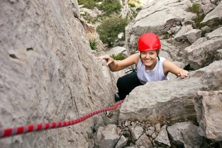 climbing: Retrato de mujer alegre escalador subiendo una roca Foto de archivo
