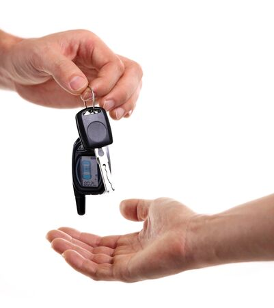 Male hand holding a car key and handing it over to another person Stock Photo - 17344875