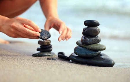 Cropped image of young woman building stone tower at the beach photo