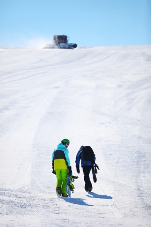 Two snowboarders walking up slope photo